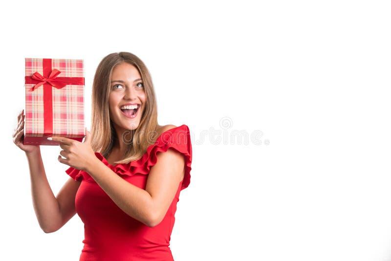 Młoda ładna dziewczyna w czerwieni sukni mienia teraźniejszość odosobniony zdjęcia stock