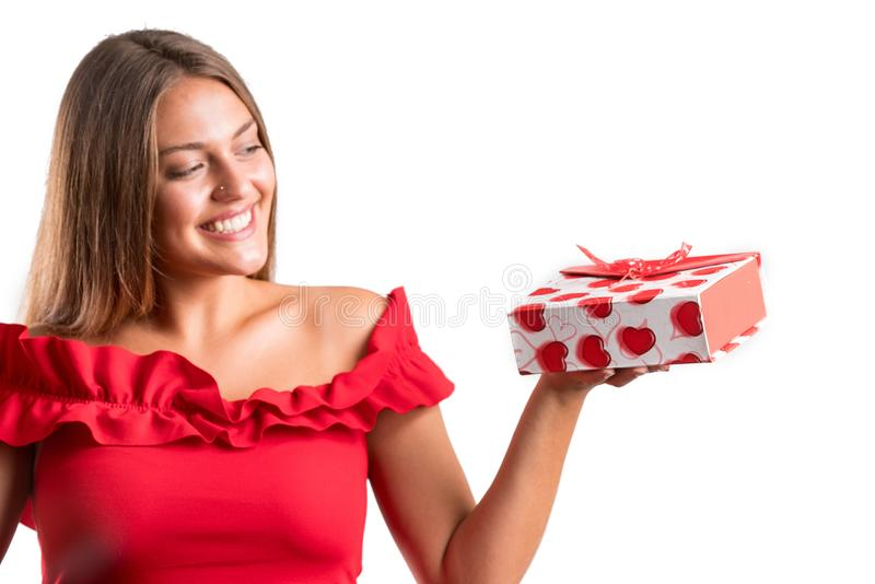 Młoda ładna dziewczyna w czerwieni sukni mienia teraźniejszość odosobniony fotografia royalty free
