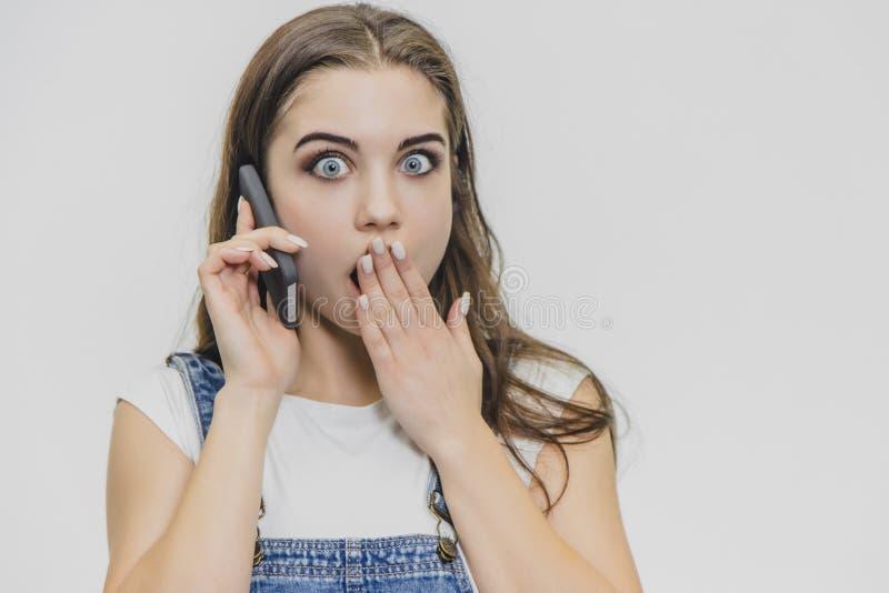 Młoda ładna dziewczyna w górę ubierający w błękitnym drelichowym kostiumu i białej koszulce Opowiadać na telefonie z inną ręką obrazy royalty free