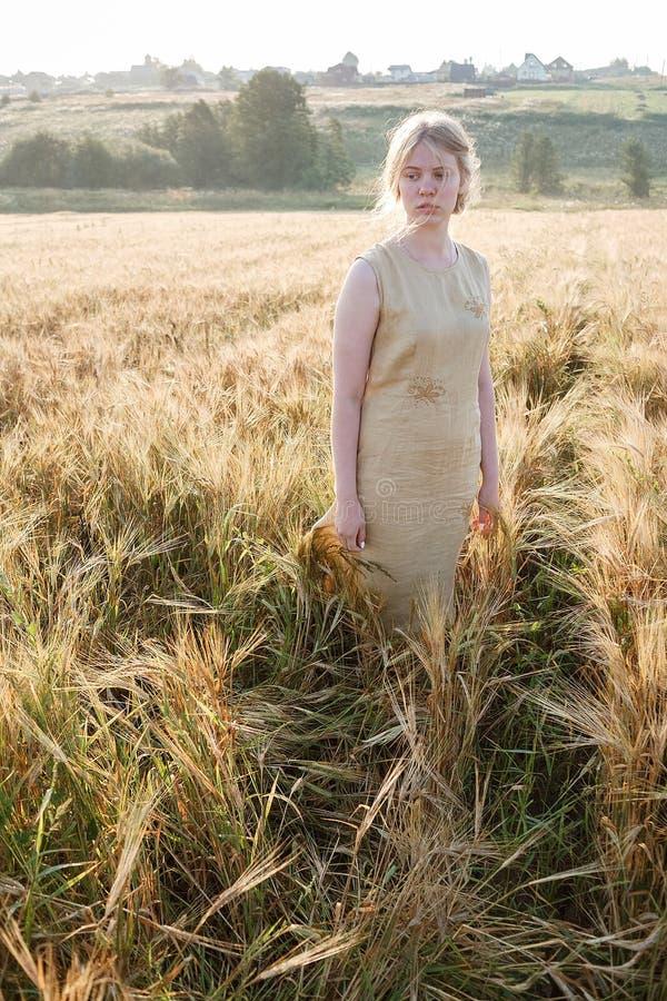Młoda ładna dziewczyna w kolor żółty sukni stojakach przy polem ucho w promieniach powstający słońce gaj i wioska w tle obraz stock