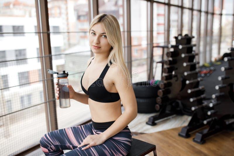 Młoda, ładna dziewczyny blondynki napojów woda po ćwiczyć w gym, aktywny tryb ?ycia Sporty w gym fotografia royalty free
