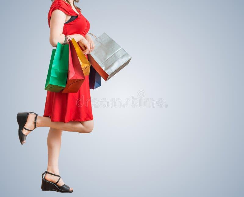 Młoda ładna kobieta jest chodząca i robiąca zakupy z kolorowymi torbami obrazy royalty free