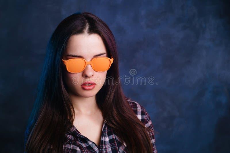 Młoda ładna kobieta jest ubranym jaskrawej pomarańcze projektował okulary przeciwsłonecznych fotografia stock