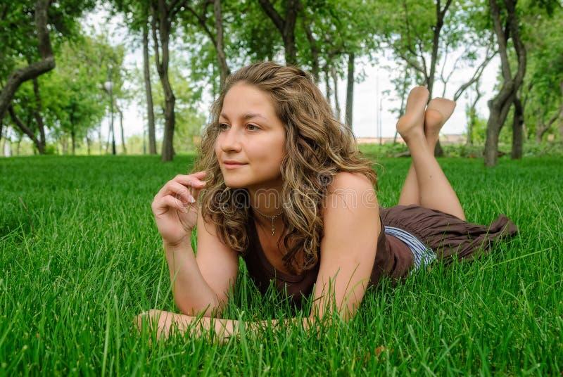 Młoda ładna kobieta kłaść na trawie obraz stock