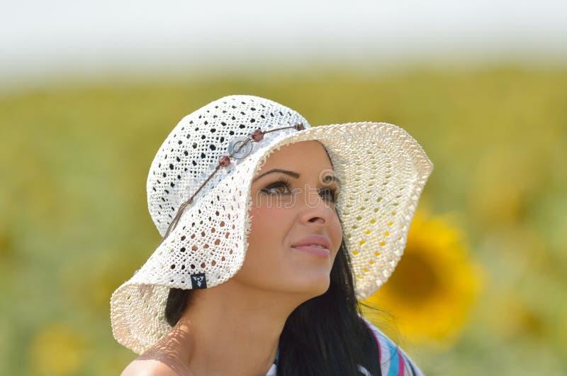 Młoda ładna kobieta na kwitnącym słonecznika polu w lecie obraz royalty free