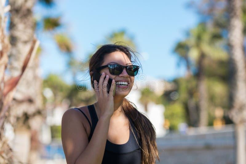 Młoda ładna kobieta opowiada na mobilny ono uśmiecha się zdjęcia royalty free