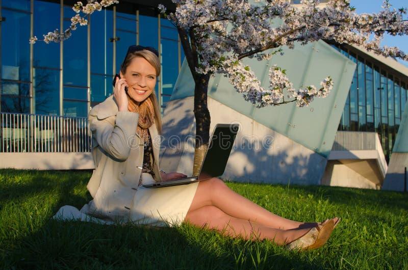 Młoda ładna kobieta opowiada telefon komórkowego z laptopem zdjęcie royalty free
