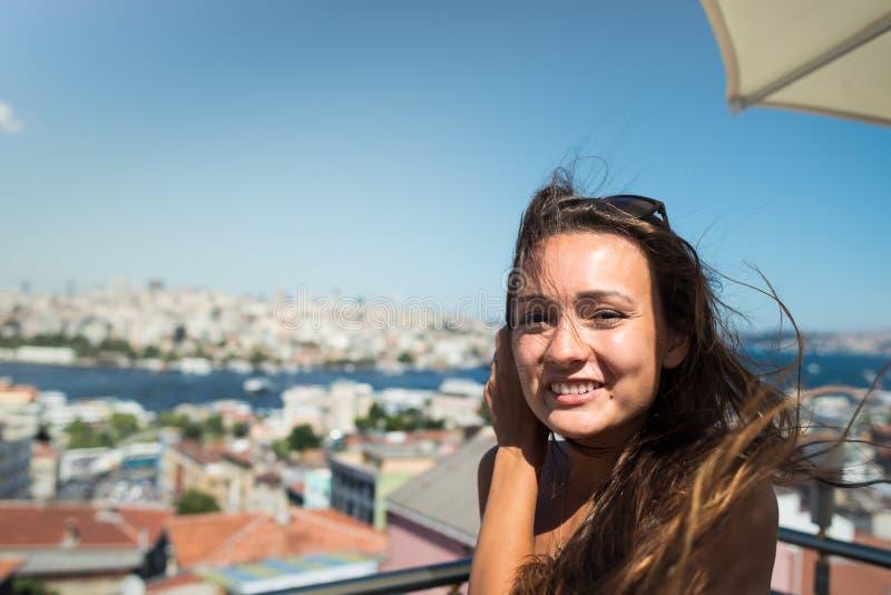 Młoda ładna kobieta siedzi na tarasie z pięknym widokiem na pejzażu miejskim zdjęcie stock