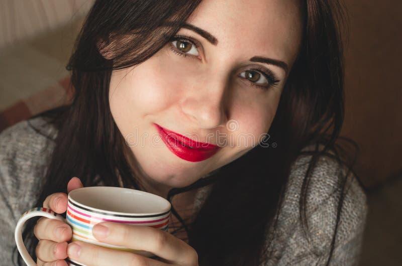 Młoda ładna kobieta trzyma filiżankę herbata w ciepłym pulowerze obrazy royalty free