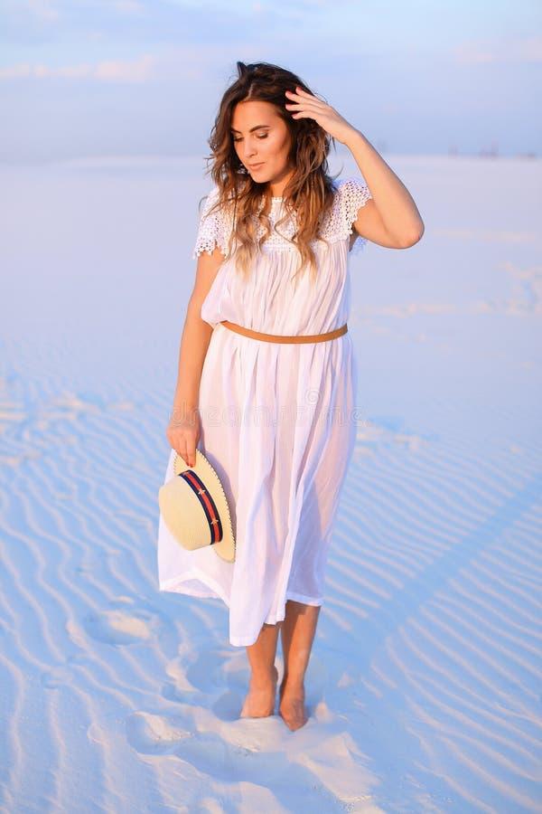 Młoda ładna kobieta utrzymuje kapelusz, będący ubranym suknię i pozycję na sa obrazy stock