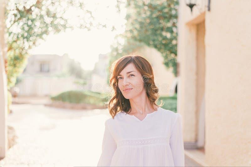 M?oda ?adna kobieta w biel sukni chodzi w starej miasto ulicie w zmierzchu zdjęcia stock