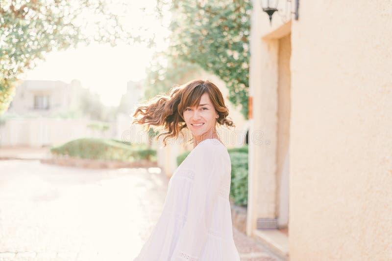 M?oda ?adna kobieta w biel sukni chodzi w starej miasto ulicie w zmierzchu fotografia royalty free