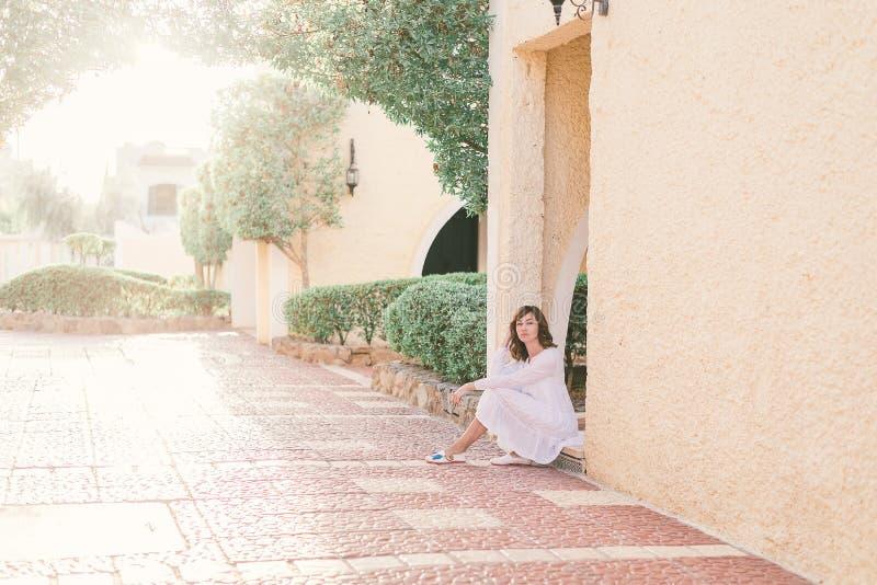 M?oda ?adna kobieta w biel sukni chodzi w starej miasto ulicie w zmierzchu obrazy stock