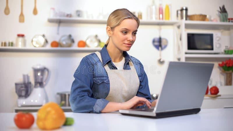 Młoda ładna kobieta w fartucha gmerania przepisu karmowych instrukcjach w interneta blogu zdjęcia royalty free