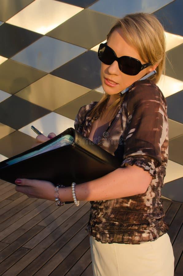 Młoda ładna kobieta z dokumentu segregatorem opowiada telefon komórkowego obraz stock