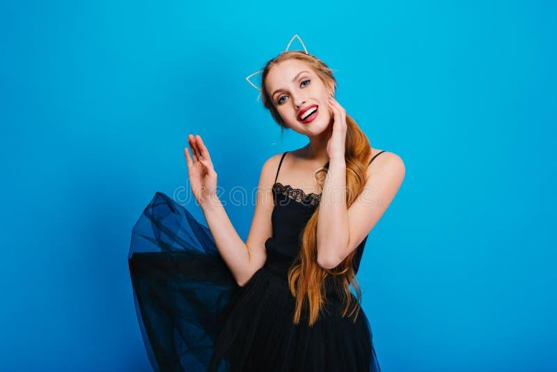 Młoda ładna kobieta z pięknym uśmiechem, trzepotliwa czerni suknia, pozuje na błękitnym tle Długie włosy, będący ubranym obrazy royalty free