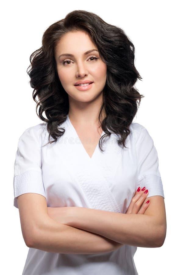 Młoda ładna kobiety lekarka utrzymuje ręki krzyżować i patrzeje kamerę odizolowywającą na białym tle w mundurze zdjęcie royalty free