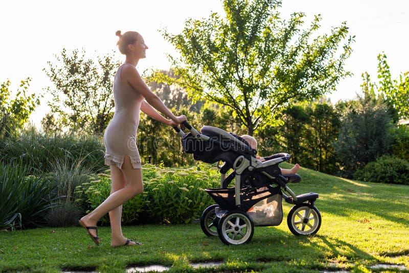 Młoda ładna matka z dzieckiem w spacerowiczu cieszy się chodzić w zielonym świeżym ogródzie przy zmierzchem Mama ma zabawę z dzie fotografia stock