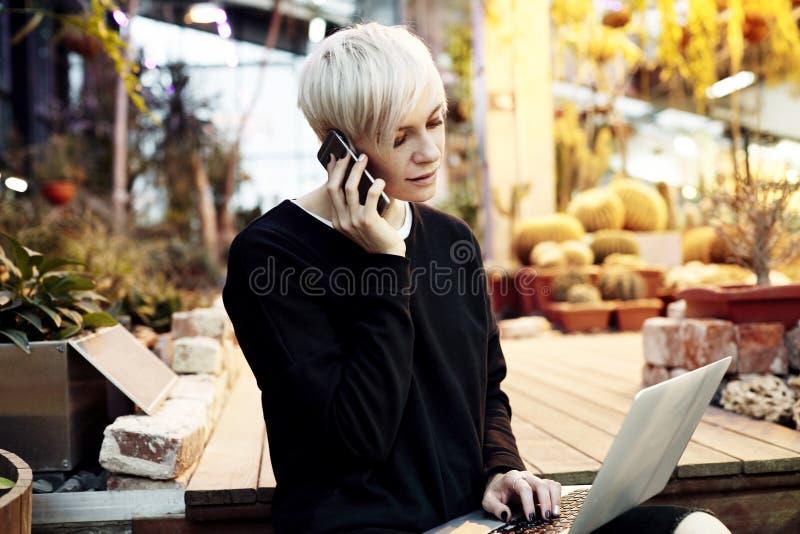 Młoda ładna modniś kobieta z blondynka krótkiego włosy obsiadaniem na schodkach, opowiada telefonem komórkowym pracuje na laptopi zdjęcia royalty free