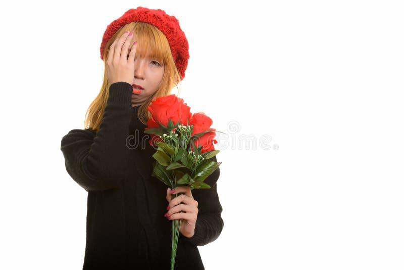 Młoda śliczna Azjatycka kobieta trzyma czerwone róże patrzeje stresujący się zdjęcia stock