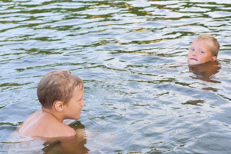 Młoda śliczna chłopiec i jego młodszy brat bawić się w wodzie w pięknym jeziorze na pogodnym letnim dniu lub rzece zdjęcia stock