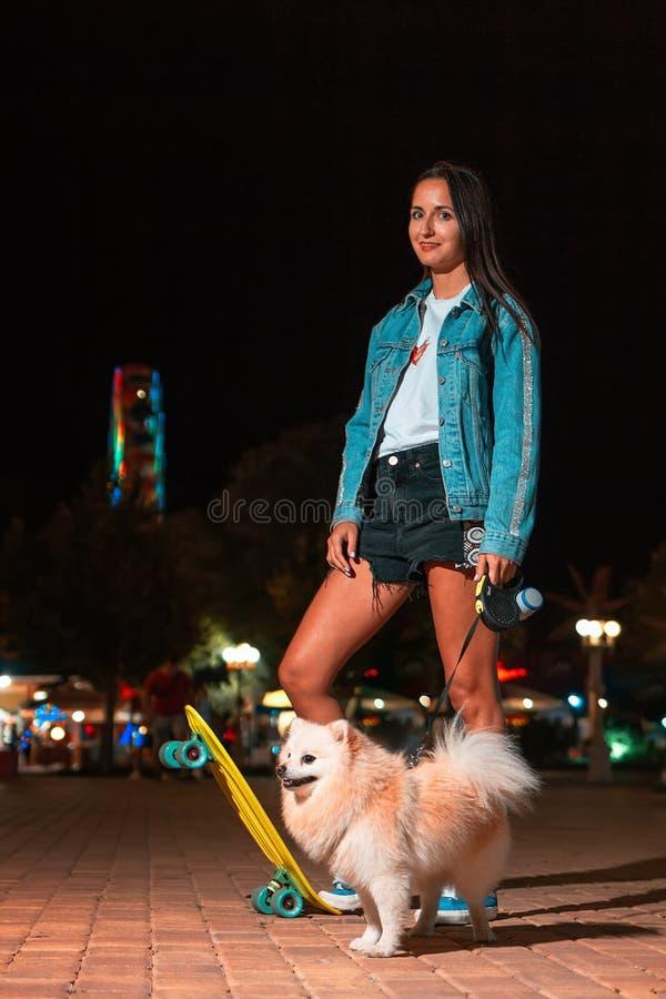 Młoda śliczna dziewczyna pozuje z deskorolka i Niemiecki Spitz pies hodujemy Tam jest park rozrywki w tle Poj?cie o obrazy royalty free
