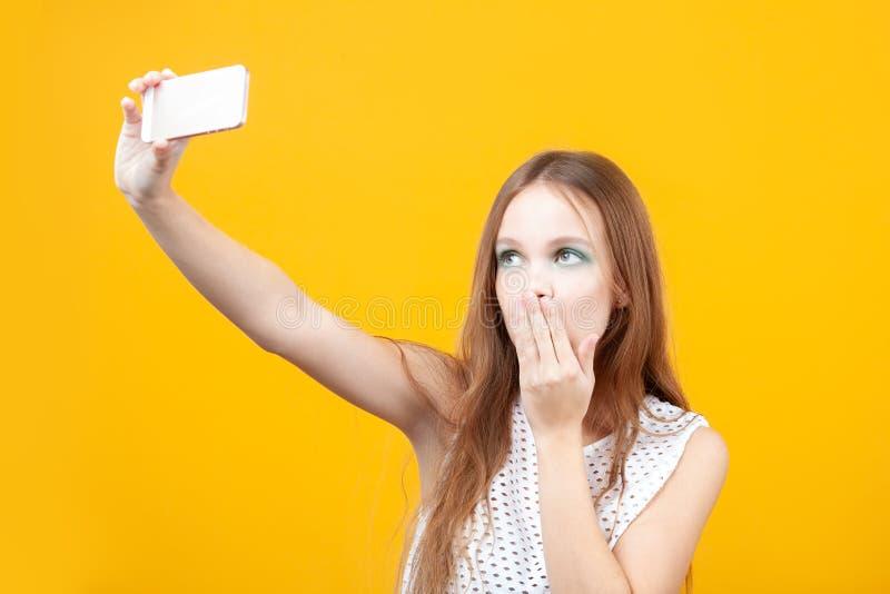 Młoda śliczna dziewczyna uśmiecha się selfie i robi używać telefon obraz stock