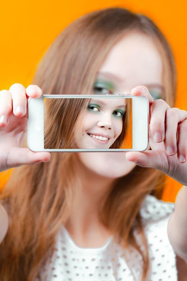 Młoda śliczna dziewczyna uśmiecha się selfie i robi używać telefon fotografia stock