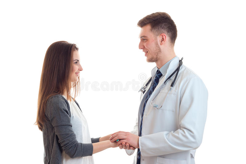 Młoda śliczna dziewczyna z długie włosy stojakami naprzeciw lekarki trzyma jego je i rękę ` ponowny ono uśmiecha się obrazy royalty free