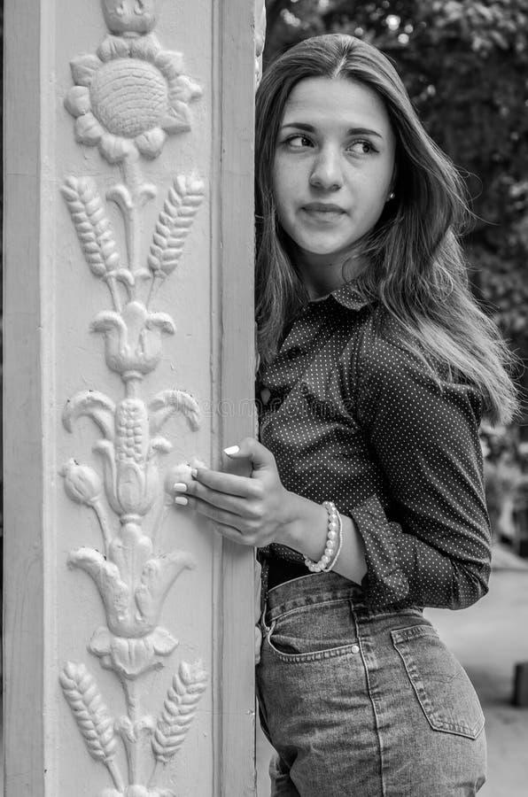 Młoda śliczna dziewczyna z długie włosy w drelichu i koszula zwiera odprowadzenie w parku w Lviv Striysky pogodnym letnim dniu po zdjęcie royalty free