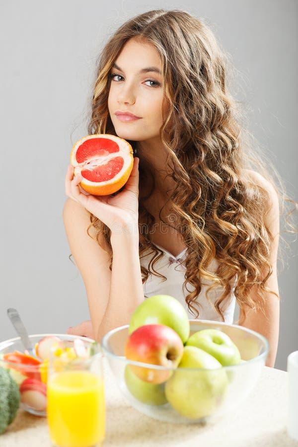 Młoda śliczna dziewczyna z grapefruitowym obrazy royalty free