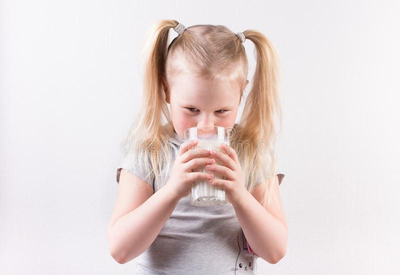 Młoda śliczna mała blondynki dziewczyna uśmiecha się szkło mleko i trzyma w białej koszulce obraz stock