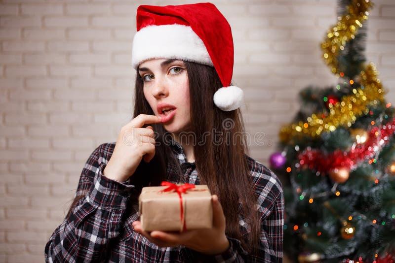 Młoda śliczna seksowna kobieta zgadywa prezent na bożych narodzeniach w Santa nakrętce zdjęcia royalty free
