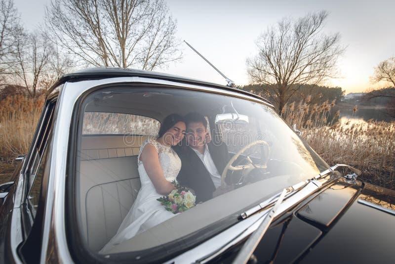 Młoda ślub para siedzi ono uśmiecha się wśrodku retro samochodu i patrzeć each inny właśnie zamężny uścisk ściska wśrodku samocho fotografia royalty free