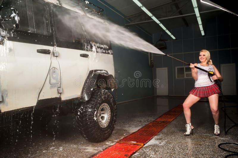 Młoda śmieszna kobieta myje offroad samochód obraz royalty free
