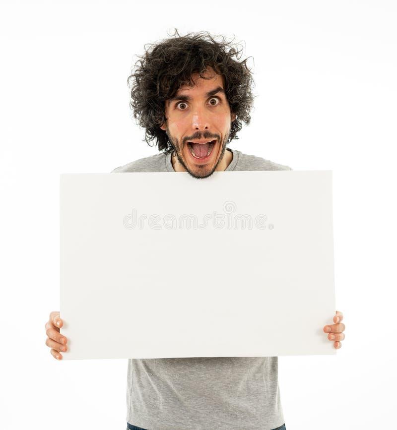 Młoda śmieszna mężczyzny mienia pustego miejsca deska dla reklamy Millennial mężczyźni wskazuje przy białym billboardem fotografia stock