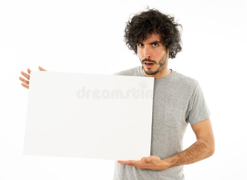 Młoda śmieszna mężczyzny mienia pustego miejsca deska z twarz seansem i sprzedawanie produktem szczęśliwym i zdziwionym zdjęcia stock