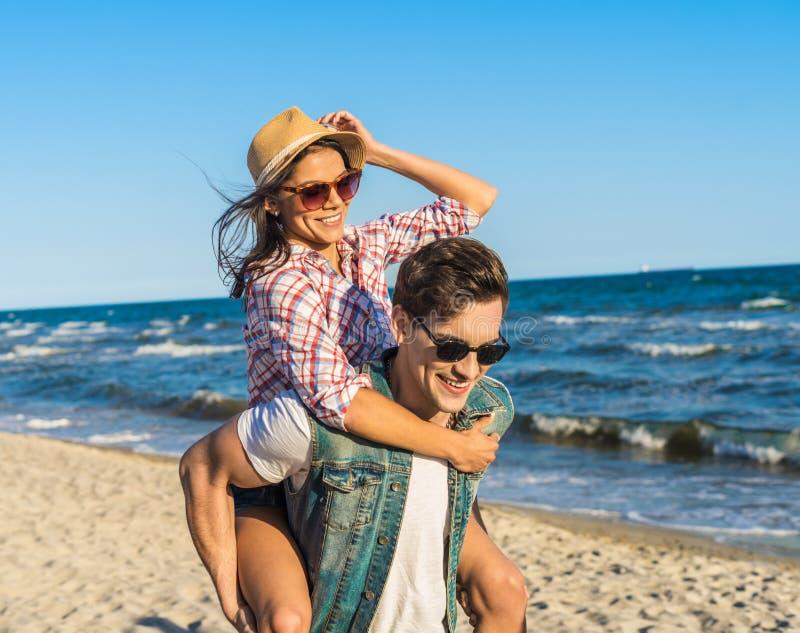 Młoda śmieszna para piggybacking na plaży w okularach przeciwsłonecznych fotografia stock