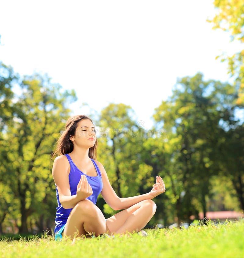 Młoda żeńska atleta w sportswear medytować sadzam na trawie fotografia royalty free