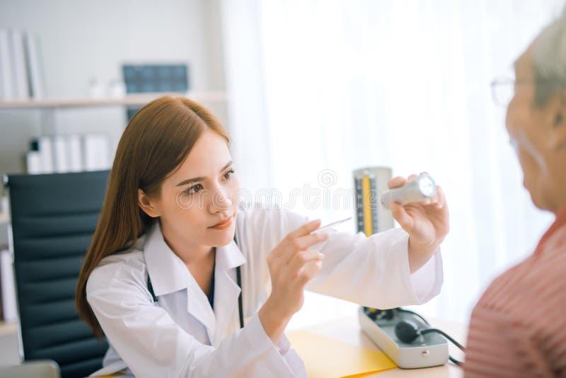 Młoda żeńska azjata lekarka sprawdza pacjenta gardło obraz stock