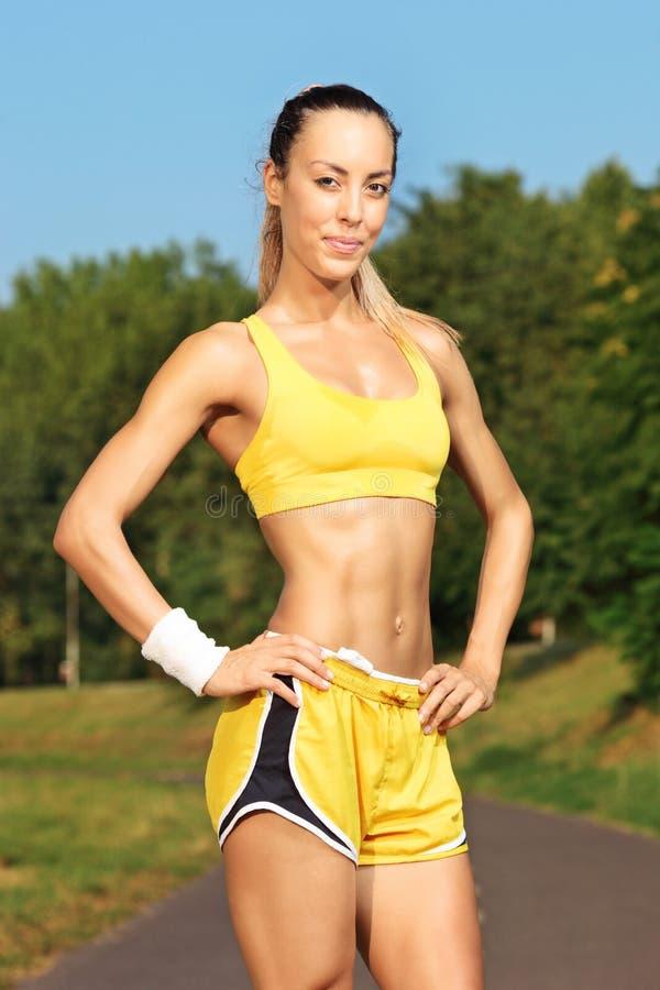Młoda żeńska biegacz pozycja na działającym śladzie fotografia royalty free
