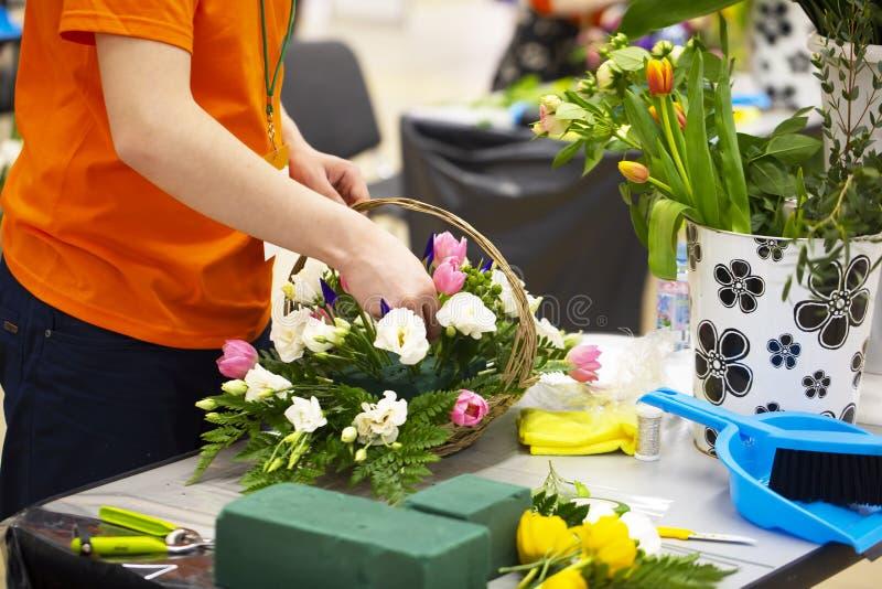 Młoda żeńska kwiaciarnia przygotowywa bukiet mieszani kwiaty podczas gdy stojący przy stołem w jej kwiatu sklepie zdjęcie stock