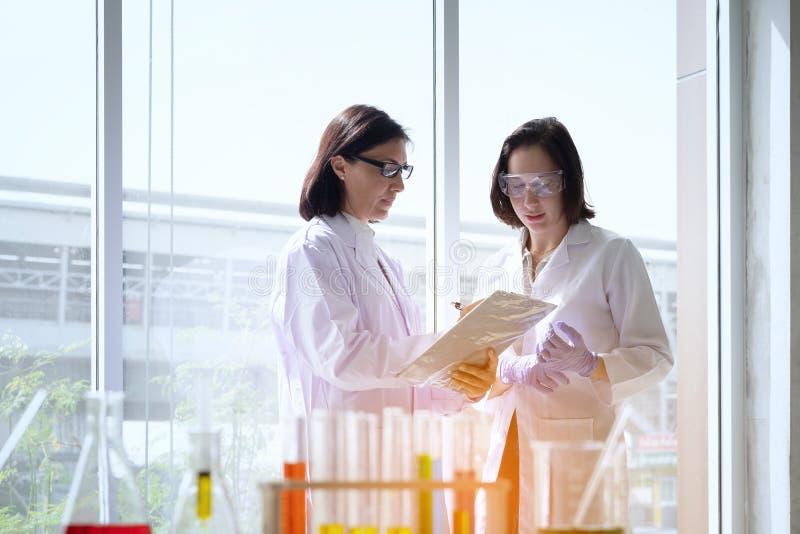 Młoda żeńska naukowiec pozycja z techer w lab pracownika robić zdjęcia stock