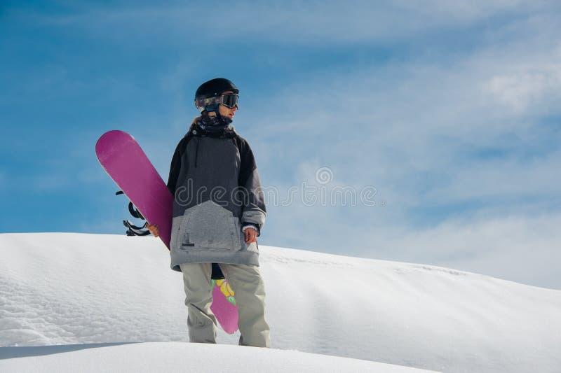 Młoda żeńska snowboarder pozycja na halnym skłonie fotografia stock
