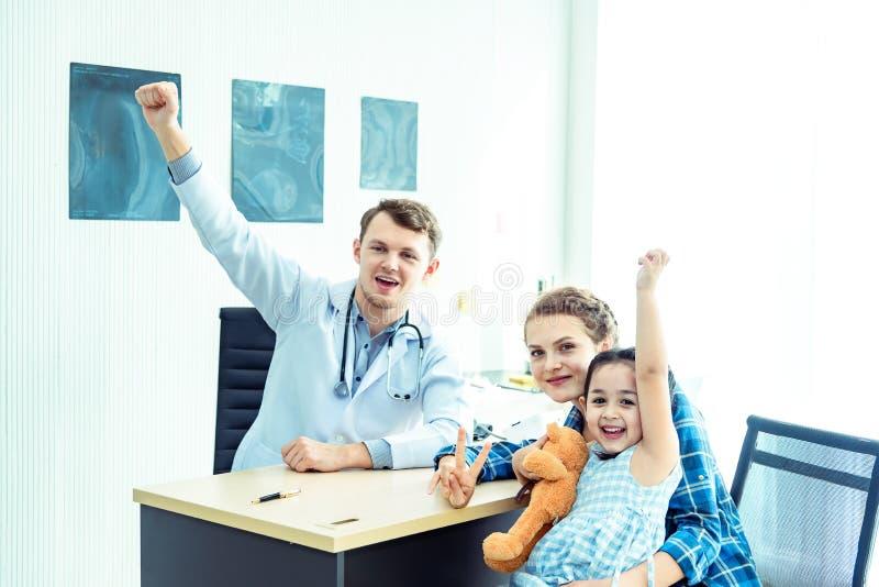 Młoda życzliwa caucasian pediatra lekarka egzamininuje dziecko cierpliwej dziewczyny z jej matką, konsultacja z stetoskopem i obraz royalty free
