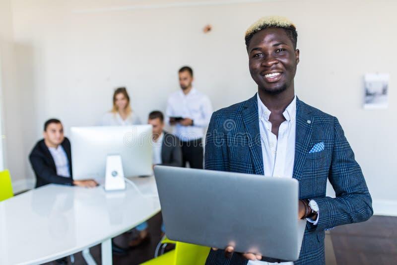 Młoda afroamerykańska lider biznesu pozycja przed biznes drużyny ono uśmiecha się zdjęcia stock
