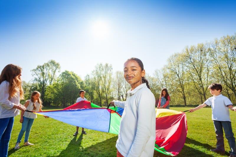 Młoda Afrykańska dziewczyna bawić się spadochron z przyjaciółmi zdjęcie royalty free