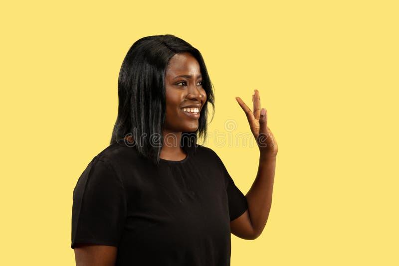 Młoda afrykańska kobieta na żółtym pracownianym tle, wyraz twarzy fotografia stock