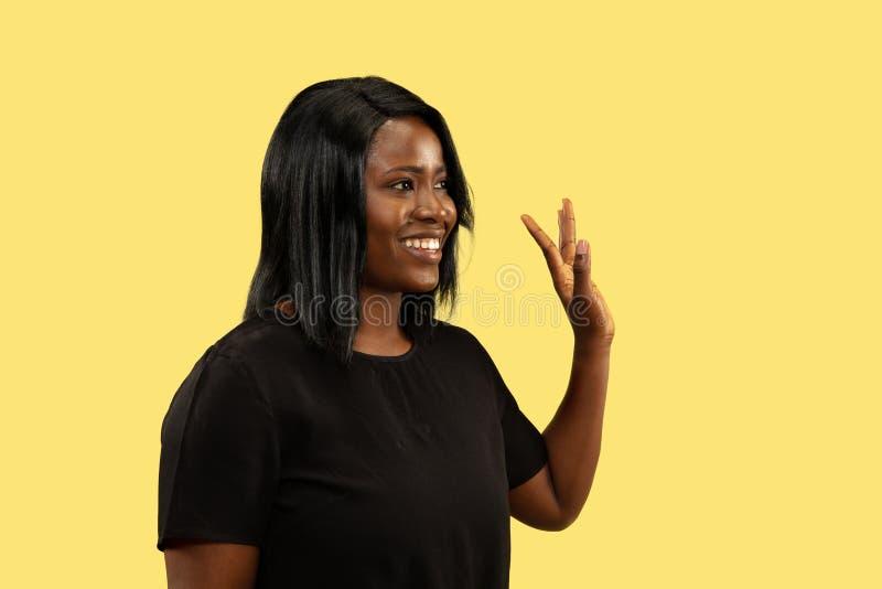 Młoda afrykańska kobieta odizolowywająca na żółtym pracownianym tle, wyraz twarzy zdjęcie royalty free