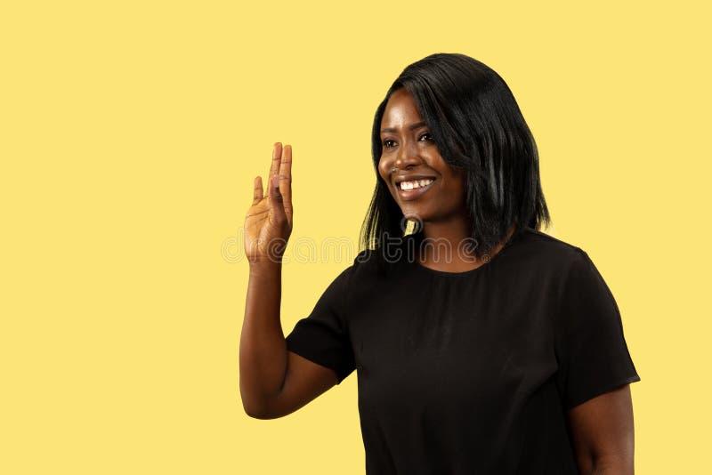 Młoda afrykańska kobieta odizolowywająca na żółtym pracownianym tle, wyraz twarzy obrazy royalty free